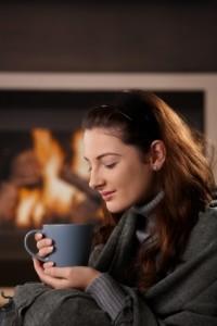 Woman sitting at fireplace